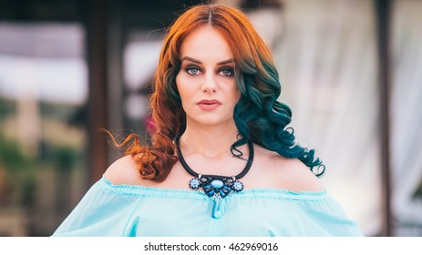 Beauty romantic girl outdoors. Beautiful model young woman with long hair on a nature. Girl with multicolored ling hair and emerald dress. Advertising picture. Close up photo