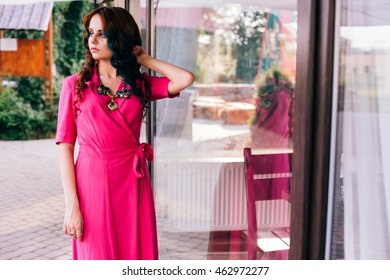 Beauty romantic girl outdoors. Beautiful model young woman with long hair on a nature. Girl with multicolored ling hair and saturated/bright pink dress. Advertising picture. Outdoor portrait near cafe