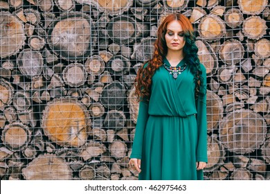 Beauty romantic girl outdoors. Beautiful model young woman with long hair on a nature wood background. Girl with multicolored ling hair and green dress. Advertising picture. Outdoor portrait near cafe
