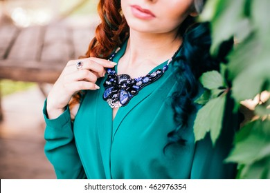 Beauty romantic girl outdoors. Beautiful model young woman with long hair on a nature wood background. Girl with multicolored ling hair and green dress. Advertising picture. Close up photo.