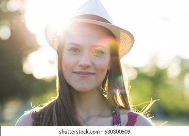 Beauty Romantic Girl Outdoors. Beautiful young brown hair model dressing a white panama hat at park in Sun Light. Summer portrait. Glow Sun, Sunshine. Backlit. Toned in warm colors
