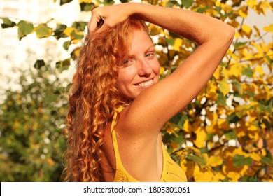 Beauty Romantic Girl Outdoors enjoying nature. Beautiful autumn model with curly hair. Sun light on sunset. Portrait of romantic female