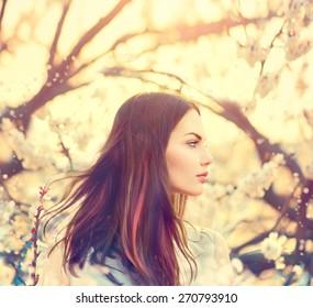Beauty Romantic Girl Outdoors enjoying nature. Beautiful Model girl with long healthy blowing hair in Spring garden, Sun Light. Glow Sun. Free Happy Woman. Toned in warm colors