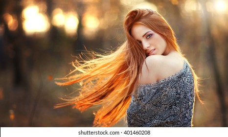 Beauty Romantic Girl Outdoors enjoying nature. Beautiful autumn red hair model with waving glow hair.Sun light on sunset.Warm toned art work. Portrait of romantic female in sweater. Photo in motion,
