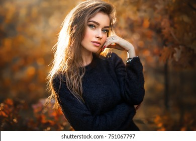 Beauty Romantic Girl Outdoors enjoying nature. Beautiful autumn model with  waving glow hair.Sun light on sunset.Warm toned art work. Portrait of romantic female