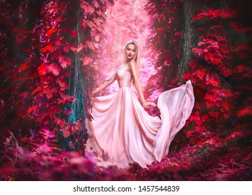 Beauty romantic young woman in long chiffon dress with gown posing in the fantasy forest in red lush. Beautiful happy bride model girl enjoying nature outdoors, fluttering dress. Autumn