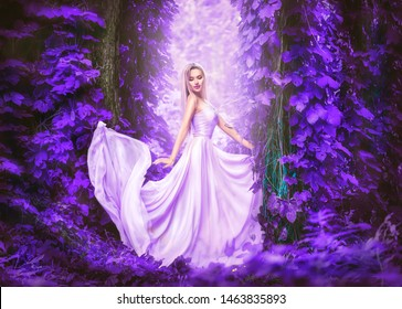 Beauty romantic young woman in long chiffon dress with gown posing in the fantasy forest in violet lush. Beautiful happy bride model girl enjoying nature outdoors, fluttering dress. Autumn garden