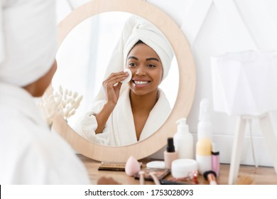 Beauty Routine. Beautiful african girl cleaning her face with cotton pad at home, wearing bathrobe and towel on head after bath, reflecting in mirror.