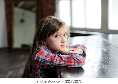 Beauty sad kid girl near the classical old piano in the retro music class