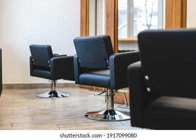 Beauty salon barbershop interior. Comfortable black leather armchairs in front of large panoramic mirrors in stylish wooden frames in a modern, cozy and bright room.