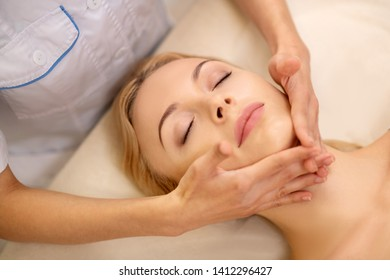 Beauty salon. Beautiful woman with natural makeup coming to beauty salon having face massage