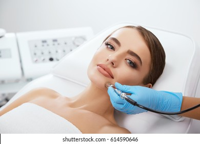 Beauty salon, doctor in blue gloves doing mechanic peeling with diamond polishing. Microdermabrasia, head and shoulders of beautiful woman with blue eyes, closeup