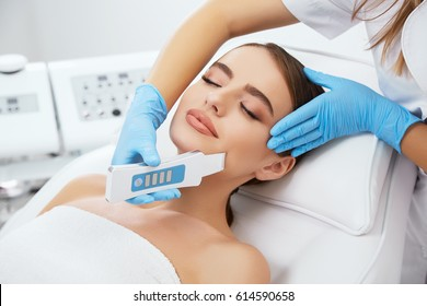 Beauty salon, doctor in blue gloves doing dermatologic procedures with ultra sonic scraber. Cosmetology, head and shoulders of beautiful woman with closed eyes, closeup
