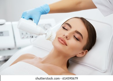 Beauty salon, doctor in blue gloves doing dermatologic procedures with Brushing. Brossage, head and shoulders of beautiful woman with closed eyes and hands of doctor