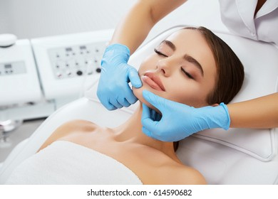 Beauty salon, doctor in blue gloves massaging face of beautiful woman, only hands. Dermatologic procedures, head and shoulders of girl with closed eyes, closeup
