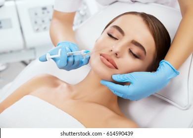 Beauty salon, doctor's hands in blue gloves holding syrringe with filler near girl's face. Contouring plastic surgery, head and shoulders of beautiful woman with closed eyes, closeup