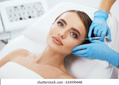 Beauty salon, doctor's hands in blue gloves holding syrringe with filler near girl's eyes. Contouring plastic surgery, head and shoulders of beautiful woman with blue eyes, closeup