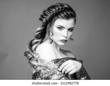 Beauty salon hairdresser art. Girl makeup face braided long hair. French braid. Professional hair care and creating hairstyle. Braided hairstyle. Beautiful young woman with modern hairstyle.