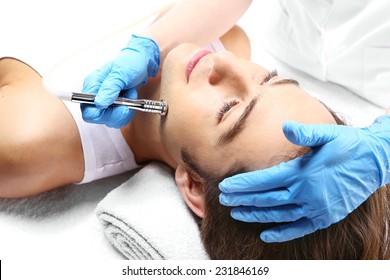 Beauty salon, microdermabrasion. Handsome man during microdermabrasion treatment in beauty salon
