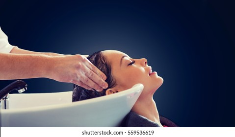 beauty salon and people concept - happy young woman and hairdresser hands washing head and hair over blank black background