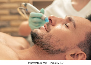 Beauty salon skin nourishing procedure and young bearded man relaxing with closed eyes