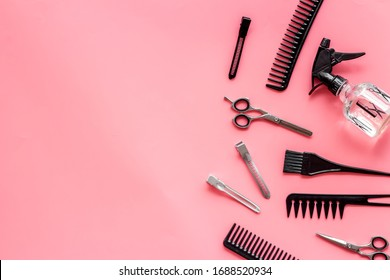 Beauty saloon accessories - combs, sciccors for hairdressing - on pink background top-down frame copy space
