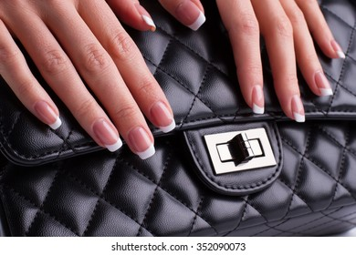 Beauty saloon. Beautiful french manicure on a background of black leather bag.