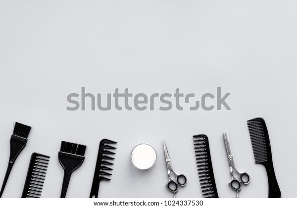 Beauty saloon equipment. Hairdress, haircut. Combs, sciccors, brushes on grey background top view copy space