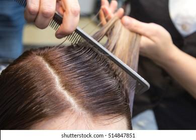Beauty saloon. Girl combing her hair