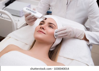 Beauty saves the world! Pleased young gorgeous woman lying in the salon and getting the facial recovery.