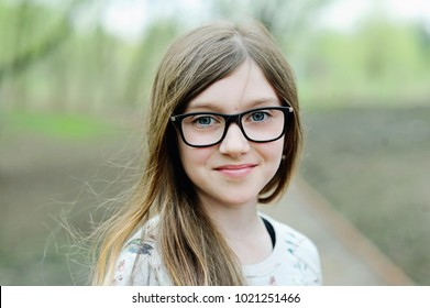 Beauty school aged brunette girl in glasses in beauty spring park on sunny warm day