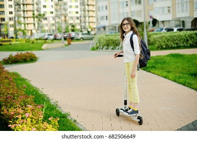 Beauty school aged kid girl in glasses and long hair with backpack ridding her scooter on city streets