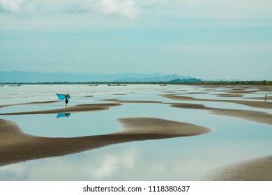 Beauty of seascape vista at low tide with blue cloudy sky and turquoise water.
