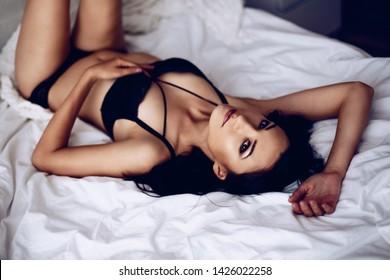 Beauty seductive brunette woman in black lingerie in bed