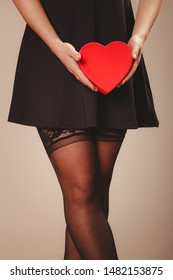 Beauty, sexuality and seductiveness. Sexy part body woman wearing black dress and stockings panties holding red heart box present gift in hands. Studio shot.