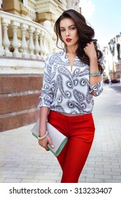 Beauty sexy brunette woman dark long hair evening makeup red lipstick wearing silk blouse pants Autumn Collection summer fashion style accessories jewelry watches handbag walking street meeting party