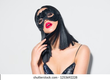 Beauty sexy Glamour brunette Woman portrait. Girl wearing carnival black feather mask. Party. Black hair, red lips, holiday makeup. Christmas and New Year celebration