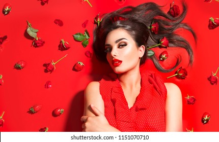 Beauty Sexy Model girl lying on red background with rose flowers and strawberries. Beautiful brunette young woman with long hair and perfect make-up, red seductive lips, smoky eyes. Trendy makeup
