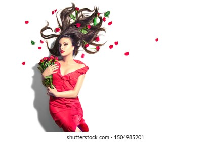 Beauty Sexy Model girl lying on white background with red rose flowers in her hair and a bunch. Beautiful young woman with long hair and perfect make-up, red seductive lips, smoky eyes. Birthday Gift