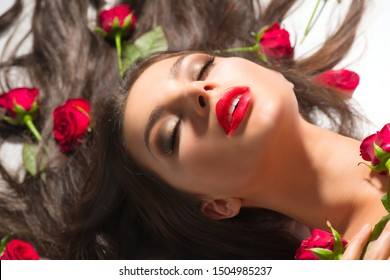 Beauty Sexy Model girl lying on white background with red rose flowers in her hair. Beautiful brunette young woman with long hair and perfect make-up, red seductive lips, smoky eyes. Makeup