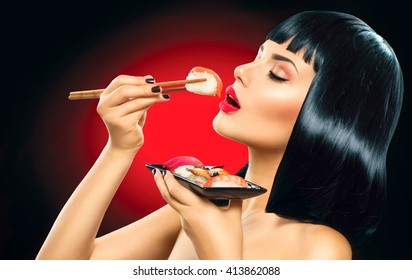 Beauty sexy woman eating sushi. Sushi rolls, sashimi. Fashion model girl eating Sushi with chopsticks. Perfect make up and bob haircut, eating healthy japanese food. Diet, dieting concept.