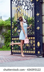 Beauty sexy woman fashion model glamour style clothes casual dress for party and office accessory lather bag and silk wrap brand sunglasses street look garden yard green trees gate summer collection