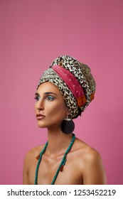 Beauty shoot of african woman standing against pink background. Portrait of african woman with headscarf on her head.