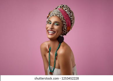 Beauty shoot of african woman standing against pink background. Portrait of african woman smiling