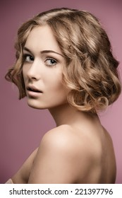beauty shoot of pretty girl with short curly blonde hair-cut and natural make-up.
