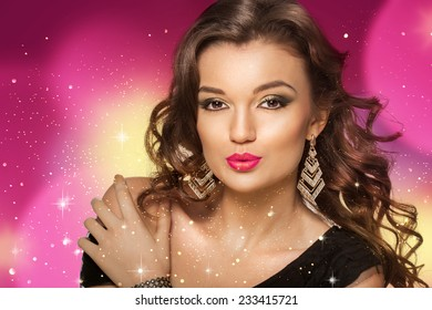 Beauty shoot of smart brunette woman in motion over colored background and sparkles. Evening makeup and dark curly hairs.