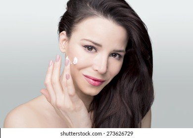 Beauty shoot of a woman on a white background applying face cream
