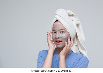 Beauty shot of Asian cute girl with beautiful skin shows mask cream on her face and holding tomato or cucumber as nutrient for treatment her facial skin