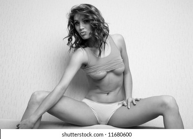 Beauty shot of a beautiful young woman on the sofa. Black and white photo.