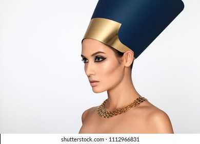 Beauty shot in Egyptian style. Beautiful adult girl in Nefertiti. Luxury and wealth. Golden decoration. Makeup, rough look. White background.